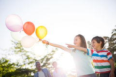 Happy siblings holding balloons at the park Royalty Free Stock Photography