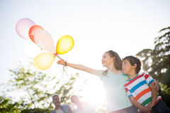 Happy siblings holding balloons at the park Royalty Free Stock Image