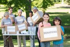 Happy siblings holding donation box. On a sunny day Royalty Free Stock Photos