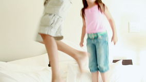 Happy siblings jumping on a mattress stock video footage