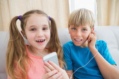 Happy siblings listening to music on sofa Stock Photography