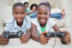 Happy siblings lying on the floor playing video games. At home in the living room royalty free stock photos