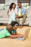 Happy siblings lying on the floor using laptop. In the living room Royalty Free Stock Photo