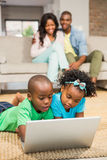 Happy siblings lying on the floor using laptop. In the living room Royalty Free Stock Photography