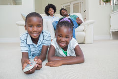 Happy siblings lying on the floor watching tv Royalty Free Stock Photo