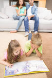 Happy siblings lying on the rug reading a storybook Stock Image