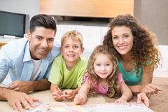 Happy siblings lying on the rug reading storybook with their parents Stock Photos