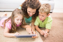 Happy siblings lying on the rug using tablet with their mother Stock Images