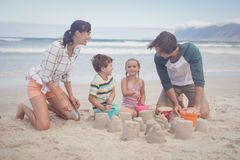 Happy siblings with parents making sand castle Royalty Free Stock Photo