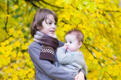 Happy siblings in park with yellow autumn leaves Royalty Free Stock Image