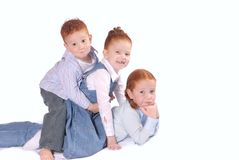 Happy siblings playing. Happy preschool boy and girl sat on older sister, isolated on white studio background Royalty Free Stock Image