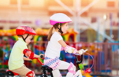 Happy siblings playing outdoors. Boy and girl riding on bicycles Stock Photo