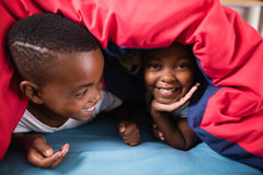 Happy siblings playing under blanket at home Royalty Free Stock Photography