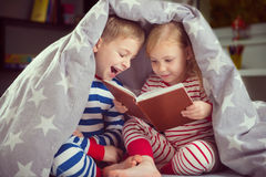 Happy siblings reading book under cover Royalty Free Stock Photography
