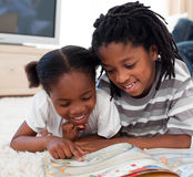Happy siblings reading lying on the floor. In the living room stock image