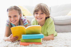 Happy siblings reding book while lying on rug Stock Photos