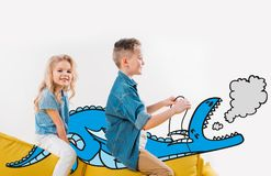 happy siblings riding drawn blue dragon while sitting stock illustration