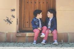 Happy siblings. Sitting on the floor Stock Image