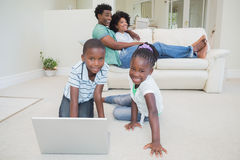 Happy siblings sitting on the floor using laptop. At home in the living room Royalty Free Stock Photos