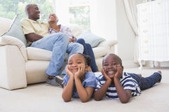 Happy siblings sitting on the floor watching television Royalty Free Stock Photography