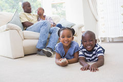 Happy siblings sitting on the floor watching television Royalty Free Stock Images