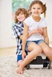 Happy siblings sitting on vacuum cleaner Royalty Free Stock Photo