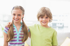 Happy siblings standing arm around at home. Portrait of happy siblings standing arm around at home royalty free stock image