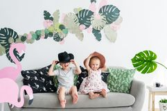 Happy siblings in straw hats sitting on sofa at home. Concept of the happy childhood stock photos
