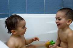Happy siblings: Two little twins children playing together with water by taking bath in bathtub at home. Kid boys having fun tog stock image