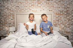 Happy siblings using joystick in bedroom Royalty Free Stock Image