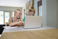 Happy Siblings Using Laptop At Home Royalty Free Stock Images