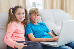 Happy siblings using laptop on sofa Stock Photos