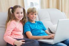 Happy siblings using laptop on sofa Stock Photos