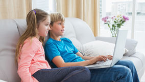 Happy siblings using laptop on sofa Royalty Free Stock Photo