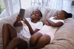 Happy siblings using mobile phone while lying on couch Royalty Free Stock Photos