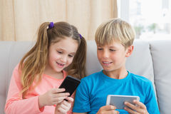Happy siblings using smartphones on sofa Royalty Free Stock Images