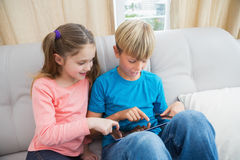 Happy siblings using tablet pc on sofa Stock Photo