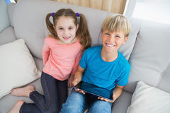 Happy siblings using tablet pc on sofa Royalty Free Stock Images