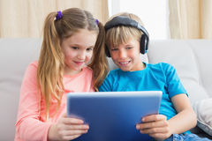 Happy siblings using tablet pc on sofa Stock Photos