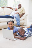 Happy siblings using their laptop Stock Photography