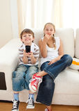 Happy siblings watching TV. On the sofa royalty free stock images