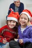 Happy Siblings Wearing Santa Hats At Home Stock Photos