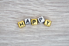 Happy sign. HAPPY cube blocks arranged on gray wooden background Stock Image