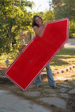 Happy sign spinning girl. A pretty young woman smiles as her hair blows in the wind. She is holding a red arrow sign to draw attention to a business Stock Images