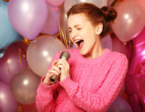 Happy singing girl. Beauty woman with microphone over  backgroun Stock Photos