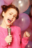 Happy singing girl. Beauty woman with microphone over  backgroun Stock Photo