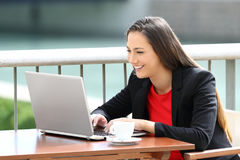 Executive woman typing in a laptop in a bar. Happy single executive woman typing in a laptop sitting in a bar stock photo