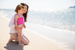 Happy single mom at the beach. Profile view of a young single mother spending a day at the beach with her daughter stock image