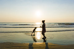 Happy single mom family silhouettes on beach. At sunset royalty free stock images