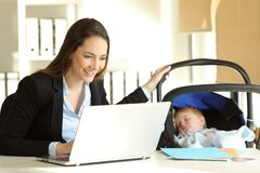 Mother working taking care of her baby at office. Happy single mother working on line and taking care of her baby at office Royalty Free Stock Photos